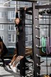 El hombre atlético brutal vestido en ropa negra de las clases levanta en la barra en el gimnasio fotos de archivo libres de regalías