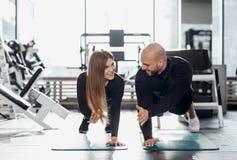 El hombre atlético brutal y la muchacha delgada joven vestidos en ropa negra de las clases están haciendo el tablón en el gimnasi fotografía de archivo