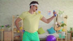 El hombre atlético divertido en el estilo de 80s es pesas de gimnasia involucradas con y presentación en la cámara metrajes