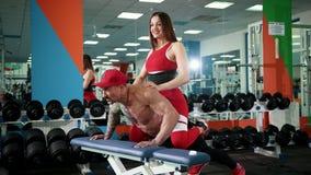 El hombre atlético en casquillo rojo en su cabeza empuja su asiento apagado, aumentando sus músculos metrajes