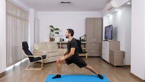 El hombre atlético en la sala de estar de su casa que hace diversa yoga presenta almacen de video