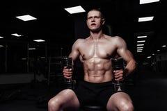 El hombre atlético fuerte hermoso que bombea para arriba muscles con pesas de gimnasia Culturista muscular con el torso desnudo d fotografía de archivo