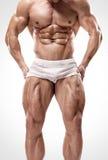 El hombre atlético fuerte muestra las piernas y los músculos abdominales Fotos de archivo libres de regalías