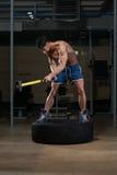 El hombre atlético golpea el neumático Foto de archivo libre de regalías