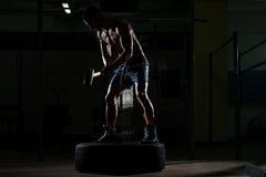 El hombre atlético golpea el neumático Imagen de archivo