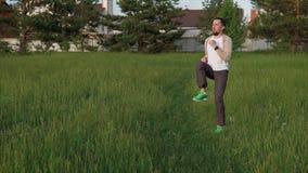 El hombre atlético hace un entrenamiento activo en el área del parque de la ciudad, él salta almacen de video