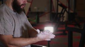 El hombre atlético hermoso aplica la magnesia a sus brazos en el gimnasio almacen de metraje de vídeo