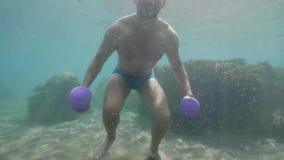 El hombre atlético joven bajo el agua está haciendo el sistema de ejercicios con pesas de gimnasia almacen de metraje de vídeo