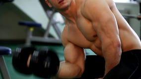 El hombre atlético joven ejecuta ejercicios del músculo almacen de metraje de vídeo