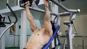 El hombre atlético joven ejecuta ejercicios del músculo metrajes