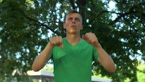 El hombre atlético que estira su brazo muscles antes de funcionamiento metrajes