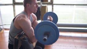 El hombre atlético que hace el bíceps se encrespa con el barbell de EZ metrajes