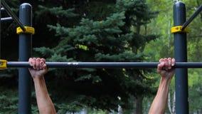 El hombre atlético que hace tirón sube en barra horizontal en parque de la ciudad Front View entrenamiento almacen de metraje de vídeo