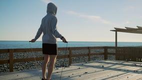 El hombre atlético se está resolviendo en la costa en el d3ia, cuerda de salto solamente almacen de metraje de vídeo