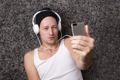 El hombre atractivo con los auriculares hace el selfie con su móvil Imagen de archivo libre de regalías