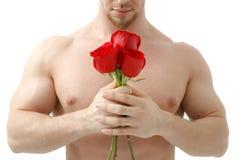 El hombre atractivo da una rosa en un fondo blanco con una luz hermosa Aislado en el fondo blanco Imagen de archivo