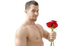 El hombre atractivo da una rosa en un fondo blanco con una luz hermosa Aislado en el fondo blanco Fotografía de archivo