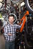El hombre atractivo en tienda de la bicicleta elige para sí mismo la bici de los deportes Foto de archivo libre de regalías