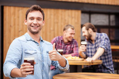 El hombre atractivo es de reclinación y que gesticula en pub Foto de archivo libre de regalías