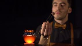 El hombre atractivo está saliendo de oscuridad, tomando el carbón de la cachimba, soplando en él, volviendo lo en el lugar e ir metrajes