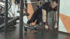 El hombre atractivo hace pectorales del crossfit con las correas de la aptitud del trx en gimnasio almacen de metraje de vídeo