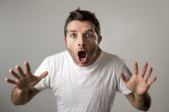 El hombre atractivo joven asombroso sorprendió en la expresión de la cara de la sorpresa del choque y la emoción del choque foto de archivo libre de regalías