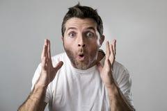 El hombre atractivo joven asombroso sorprendió en la expresión de la cara de la sorpresa del choque y la emoción del choque fotos de archivo