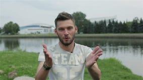 El hombre atractivo joven con una barba da una entrevista en los bancos del río almacen de metraje de vídeo