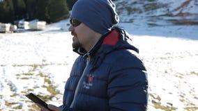 El hombre atractivo joven en ropa del invierno de los deportes corrige las gafas de sol y usar el teléfono móvil almacen de video
