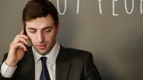 El hombre atractivo joven se sienta habla en el teléfono y el café de consumición en café almacen de video