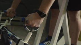 El hombre aumenta barras pesadas y pesas de gimnasia en el gimnasio almacen de metraje de vídeo