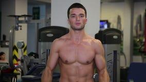 El hombre aumenta la barra en el gimnasio metrajes