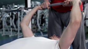 El hombre aumenta el peso libre bajo control del instructor en club de deportes El individuo hermoso miente en banco y ejercita c almacen de video