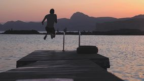 El hombre auténtico milenario joven del inconformista corre rápidamente en paseo marítimo de madera en sorprender c natural, lago metrajes