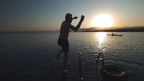 El hombre auténtico milenario joven del inconformista corre rápidamente en paseo marítimo de madera en sorprender el lago alpino  almacen de metraje de vídeo