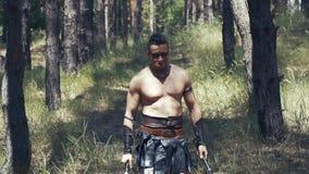 El hombre bárbaro muscular con dos hachas en sus manos está caminando en el bosque metrajes