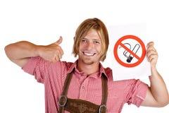 El hombre bávaro sonriente lleva a cabo la muestra de la ninguno-fumar-regla Imagen de archivo libre de regalías