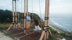 El hombre balancea a la mujer joven en el oscilación, hermosa vista del océano, cámara lenta metrajes