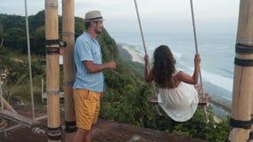 El hombre balancea a la mujer joven en el oscilación, hermosa vista del océano, cámara lenta almacen de video