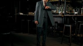 El hombre barbudo acertado serio en un traje de negocios está mirando su reloj Hombre de negocios joven cantidad 4k metrajes