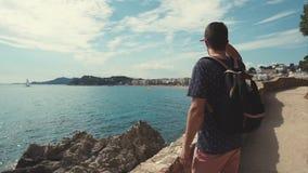 El hombre barbudo adulto está mirando en el mar en el día soleado, llevando a cabo la mano cerca de la cabeza metrajes