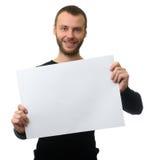 El hombre barbudo alegre muestra una hoja del papel en blanco Fotografía de archivo