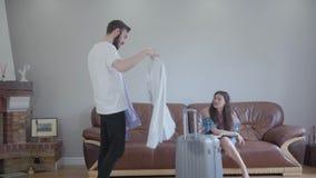 El hombre barbudo alto que pide su consejo de la esposa acerca de qu? camisa a tomar con ?l de vacaciones, ella eligi? uno El hom metrajes