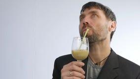 El hombre barbudo bebe el cóctel de la verdura y de la fruta smoothie del detox, concepto sano de la forma de vida Cámara lenta almacen de metraje de vídeo
