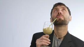 El hombre barbudo bebe el cóctel de la verdura y de la fruta smoothie del detox, concepto sano de la forma de vida Cámara lenta metrajes