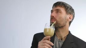 El hombre barbudo bebe el smoothie del detox, concepto sano de la forma de vida cóctel de la verdura y de la fruta Cámara lenta metrajes