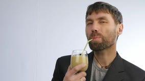 El hombre barbudo bebe el smoothie del detox, concepto sano de la forma de vida cóctel de la verdura y de la fruta Cámara lenta almacen de video