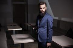 El hombre barbudo carismático se vistió en traje y con la tableta en café; Fotografía de archivo