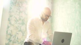 El hombre barbudo con los vidrios en blanco usando el ordenador portátil dentro Hombre de negocios que trabaja en el ordenador po almacen de metraje de vídeo