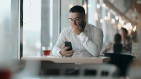 El hombre barbudo con los vidrios vio las buenas noticias en el teléfono y era feliz El hablar feliz del hombre de negocios del h almacen de video